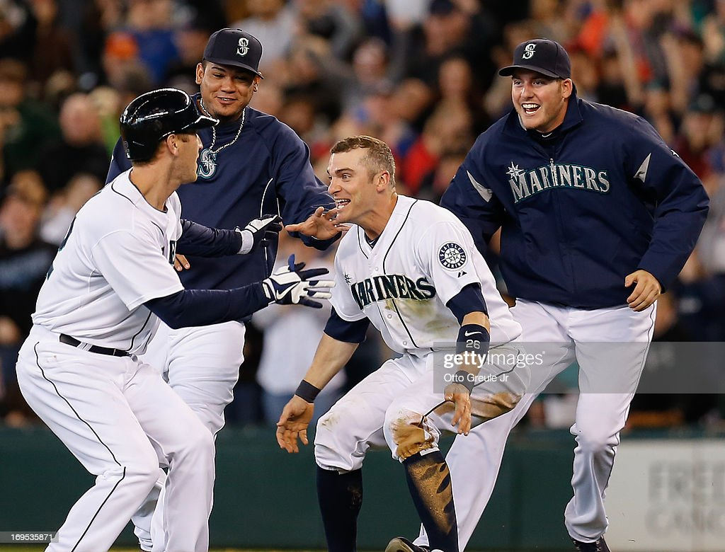 Jason Bay #12 (L) of the Seattle Mariners is congratulated by teammates after getting the game-winning hit in the thirteenth inning to defeat the Texas Rangers 4-3 at Safeco Field on May 26, 2013 in Seattle, Washington.