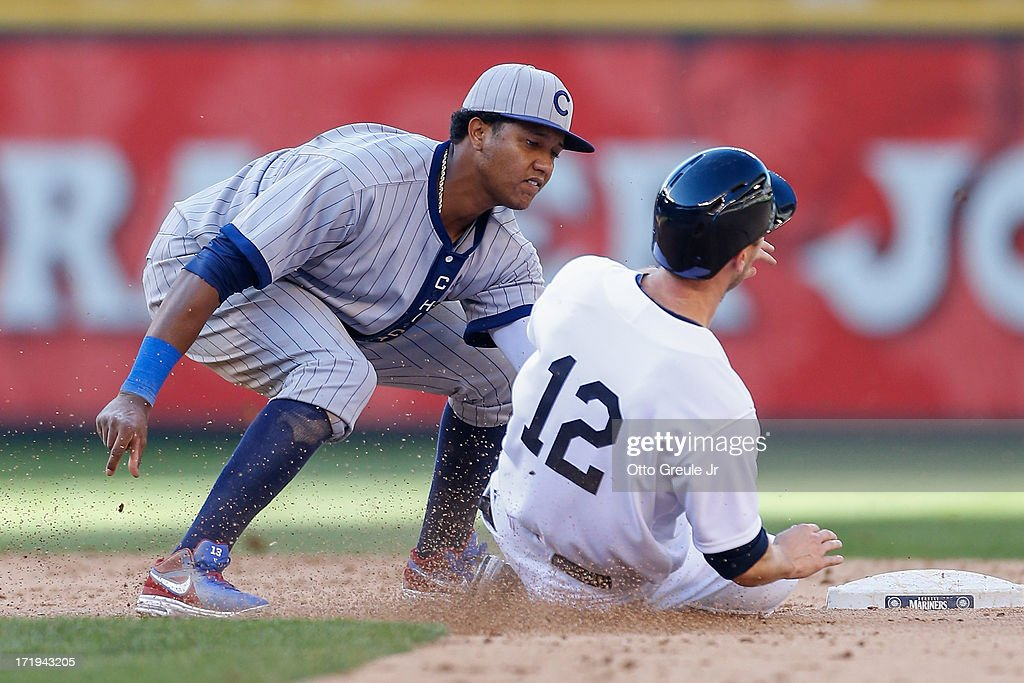Jason Bay #12 of the Seattle Mariners is tagged by shortstop Starlin Castro #13 of the Chicago Cubs after being picked off of first and trying to steal second in the eighth inning at Safeco Field on June 29, 2013 in Seattle, Washington.