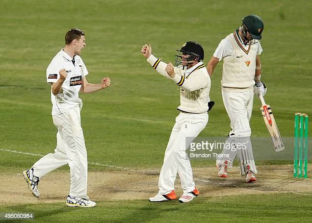 Jason Behrendorff of Western Australia celebrates with team mate Cameron Bancroft after claiming the wicket of Jackson Bird of Tasmania during day...