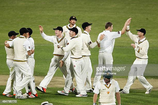 Jason Behrendorff of Western Australia celebrates with team mates after claiming the wicket of James Faulkner of Tasmania during day two of the...