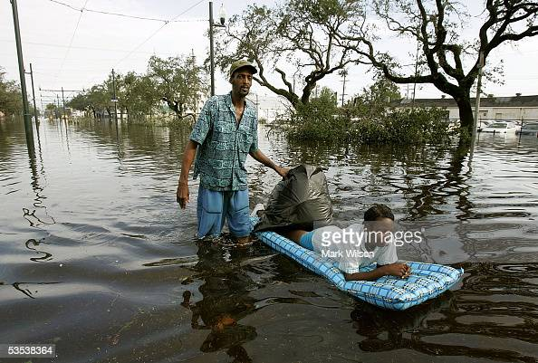 Jason Biggs pushes his wife Diane on a raft down Canal Street flooded by Hurricane Katrina August 30 2005 in New Orleans Louisiana Sixty people were...