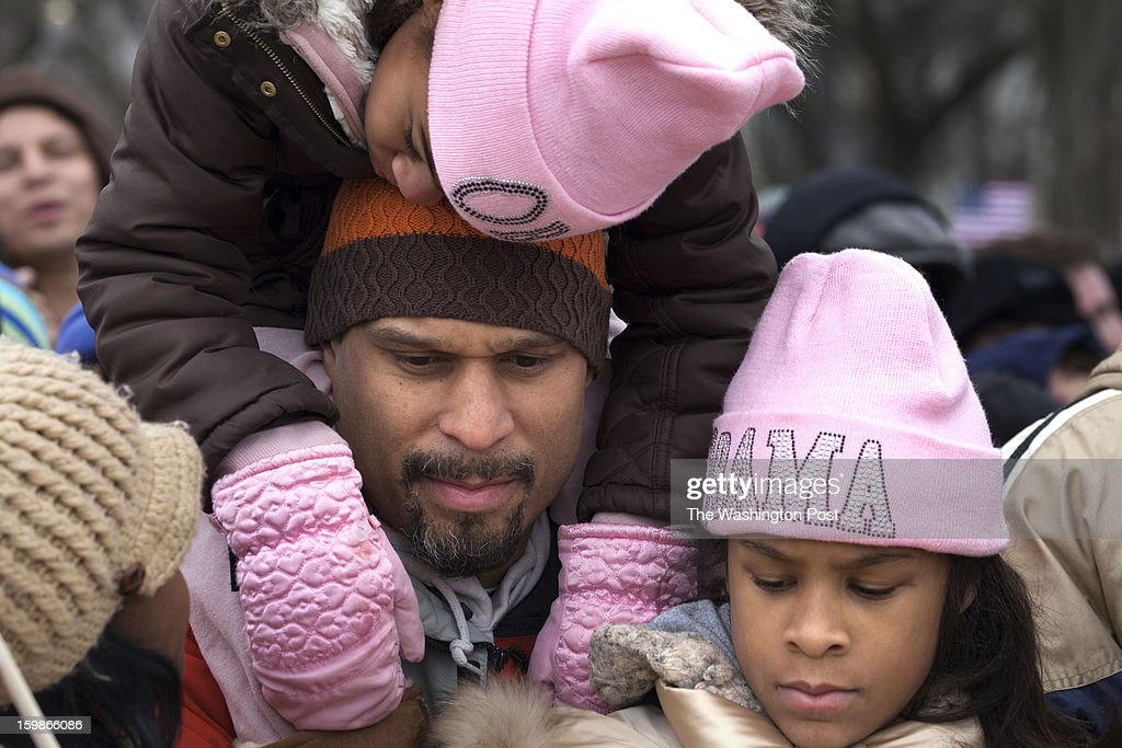 Jason Bolden (Charlotte, NC) lets one of his daughters, Nadia (7) sleep on his shoulder as his other daughter, Jaiya(9), rests in front of him during the inauguration of President Obama.