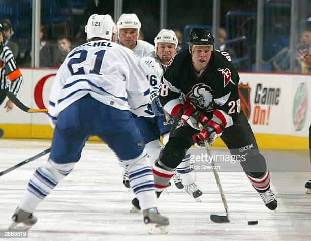 Jason Botterill of the Buffalo Sabres skates between Robert Reichel Darcy Tucker and Tie Domi of the Toronto Maple Leafs on October 30 2003 at HSBC...