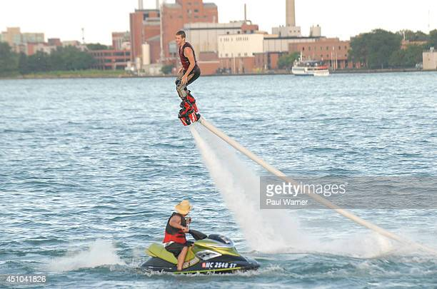 Jason Burns watches as his son Jacob Burns both of Clarkston MI rides a Flyboard during Detroit River Days 2014 at the Detroit Riverfront on June 21...