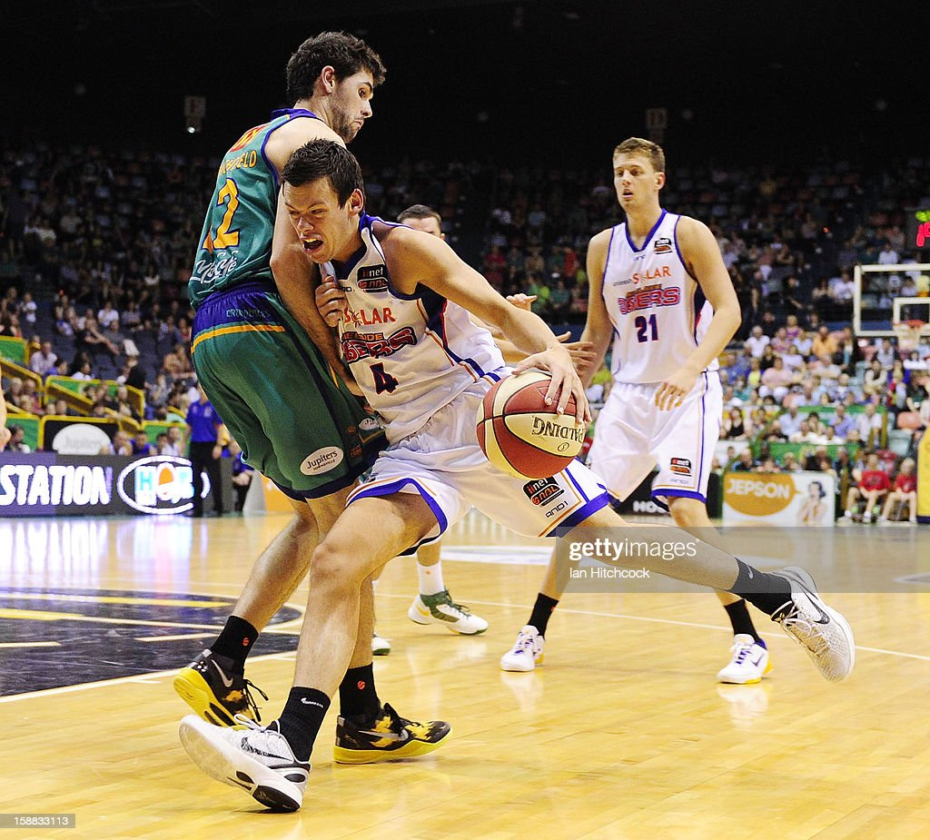 Jason Cadee of the 36ers runs into Todd Blanchfield of the Crocodiles during the round 12 NBL match between the Townsville Crocodiles and the Adelaide 36ers at Townsville Entertainment Centre on December 31, 2012 in Townsville, Australia.