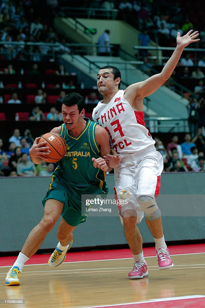 Jason Cadee (L) of the Boomers brings the ball up the court with Xi Rilijiang of China during game three of the series between the Australian Boomers and China at Tianjin Sports Center on June 12, 2013 in Tianjin, China.