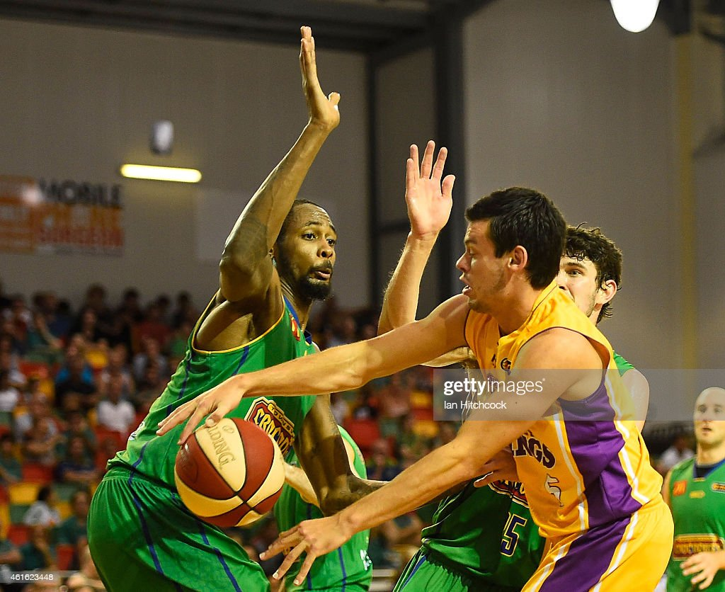 Jason Cadee of the Kings passes the ball past Mickel Gladness of the Crocodiles during the round 15 NBL match between the Townsville Crocodiles and Sydney Kings at Townsville RSL Stadium on January 16, 2015 in Townsville, Australia.