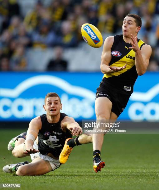 Jason Castagna of the Tigers marks the ball ahead of Liam Jones of the Blues during the 2017 AFL round 14 match between the Richmond Tigers and the...