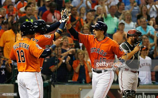 Jason Castro of the Houston Astros celebrates with teammates Marwin Gonzalez and Luis Valbuena after hitting a threerun home run in the fifth inning...