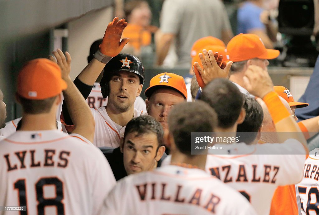 Jason Castro #15 of the Houston Astros (C) is greeted in the dugout by his temmates after his home run in the seventh inning against the Toronto Blue Jays at Minute Maid Park on August 24, 2013 in Houston, Texas.