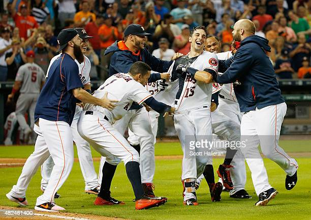 Jason Castro of the Houston Astros is mobbed by his teammates after hitting a threerun home run in the ninth inning to end the game and defeat the...