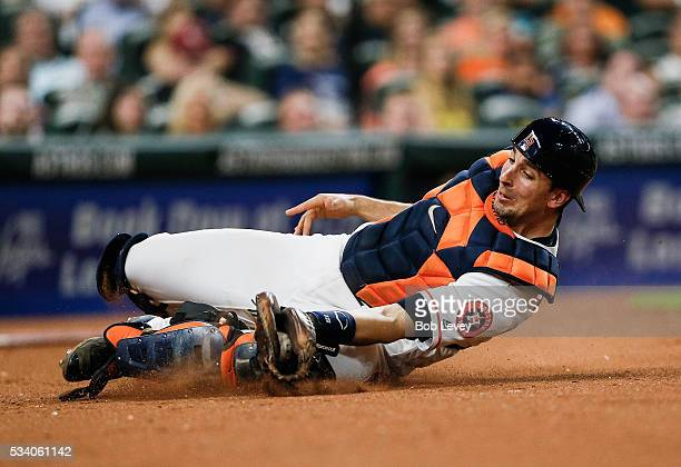 Jason Castro of the Houston Astros makes a sliding catch in foul territory in the fifth inning against the Baltimore Orioles at Minute Maid Park on...
