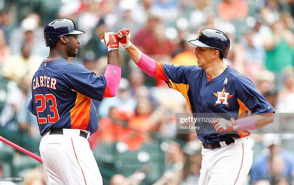 Jason Castro #15 of the Houston Astros receives a high five from Chris Carter #23 of the Houston Astros after hitting a home run in the fourth inning against the Texas Rangers at Minute Maid Park on May 12, 2013 in Houston, Texas.