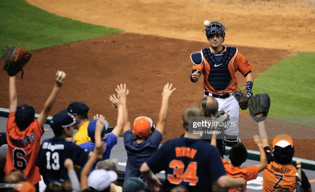 Jason Castro #15 of the Houston Astros tosses a baseball to fans in the middle of the fourth inning of their game against the Chicago White Sox at Minute Maid Park on May 16, 2014 in Houston, Texas.
