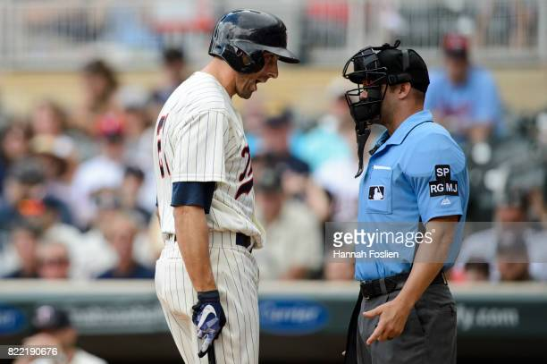 Jason Castro of the Minnesota Twins speaks to home plate umpire Will Little as he reacts to striking out against the Detroit Tigers during the game...