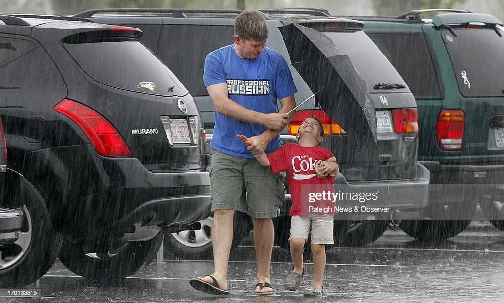 Jason Childress, left, and his son Jackson Childress, 4, have different reactions to the heavy rain as they battle rain from tropical storm Andrea before shopping at the Target store in Park Place Shopping Center in Cary, North Carolina, Friday, June 7, 2013. The storm is expected to dump inches of rain across the state.