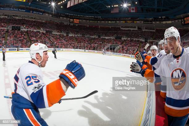 Jason Chimera of the New York Islanders pounds gloves with teammates on the bench following his third period goal during an NHL game against the...