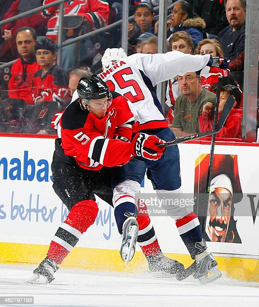 Jason Chimera of the Washington Capitals and Adam Larsson of the New Jersey Devils colide during the game at the Prudential Center on April 4 2014 in...