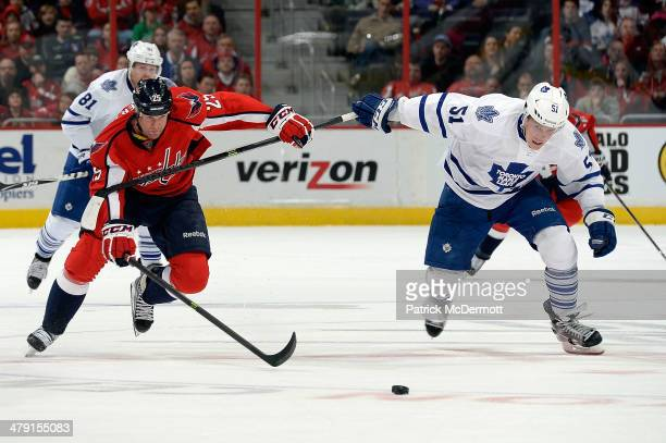 Jason Chimera of the Washington Capitals and Jake Gardiner of the Toronto Maple Leafs battle for the puck in the third period during an NHL game at...