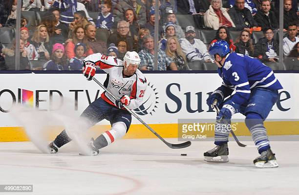 Jason Chimera of the Washington Capitals skates with the puck as Dion Phaneuf of the Toronto Maple Leafs defends during NHL game action November 28...