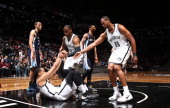 Jason Collins and Tyshawn Taylor of the Brooklyn Nets help teammate Shaun Livingston during a game against the Memphis Grizzlies at the Barclays...