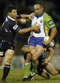 Jason Croker of the Raiders takes on the Panthers defence as Craig Gower attempts to tackle high during the round 19 NRL match between the Penrith...