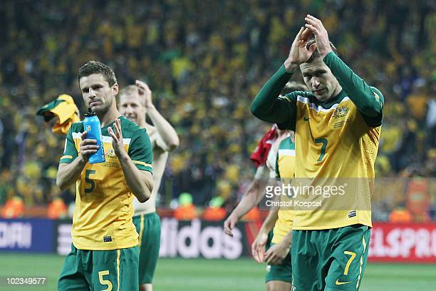 Jason Culina and Brett Emerton of Australia look dejected after victory in the game but elimination from the tournament during the 2010 FIFA World...