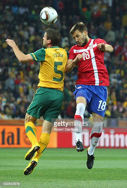 Jason Culina of Australia and Milos Ninkovic of Serbia jump for the ball during the 2010 FIFA World Cup South Africa Group D match between Australia...