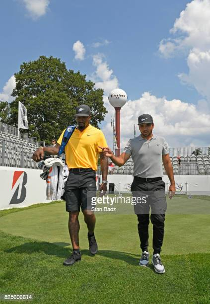 Jason Day and JR Smith of the Cleveland Cavaliers walk off the 10th tee during practice of the World Golf ChampionshipsBridgestone Invitational at...