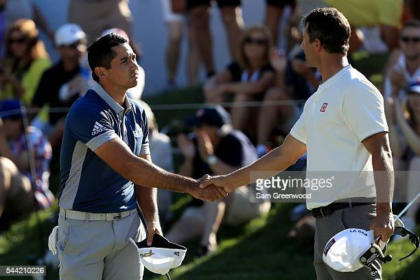 Jason Day of Australia and Adam Scott of Australia shake hands at the end of their round on the 18th green during the second round of the World Golf...