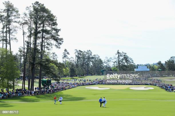 Jason Day of Australia and Augusta National member Jeff Knox the noncompeting marker approach the second green with their caddies during the third...