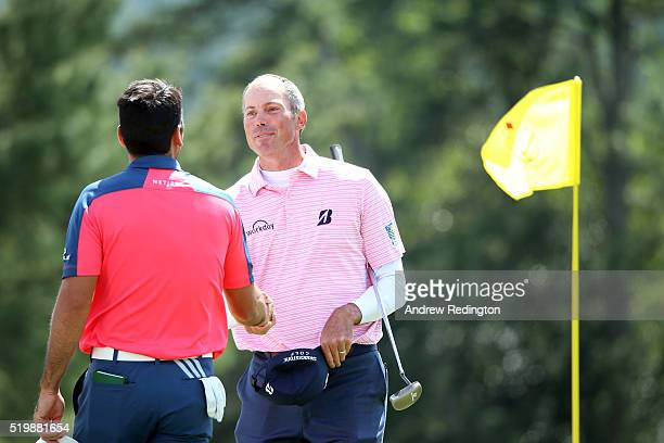 Jason Day of Australia and Matt Kuchar of the United States shake hands on the 18th green after finishing during the second round of the 2016 Masters...