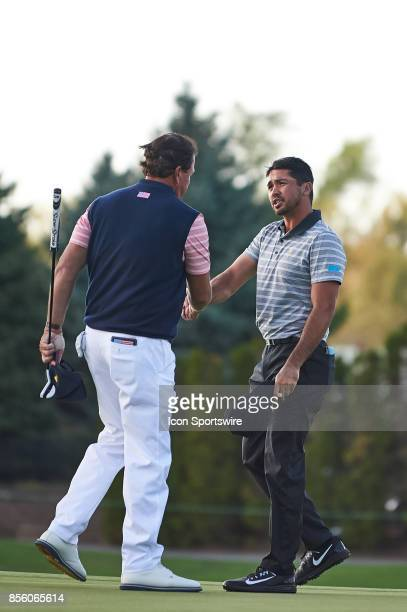 Jason Day of Australia and of the International Team shakes hands with Phil Mickelson of the American Team on the 18th green during the second round...