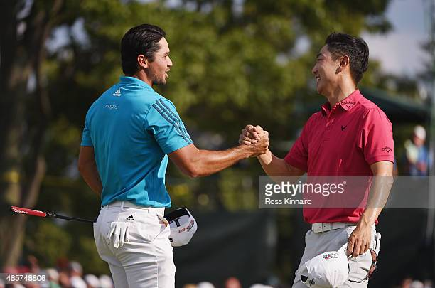 Jason Day of Australia and SangMoon Bae of Korea shake hands on the18th green during the third round of The Barclays at Plainfield Country Club on...