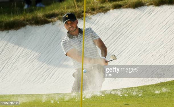 Jason Day of Australia and the International Team plays a shot from a bunker on the 14th hole during Friday fourball matches of the Presidents Cup at...