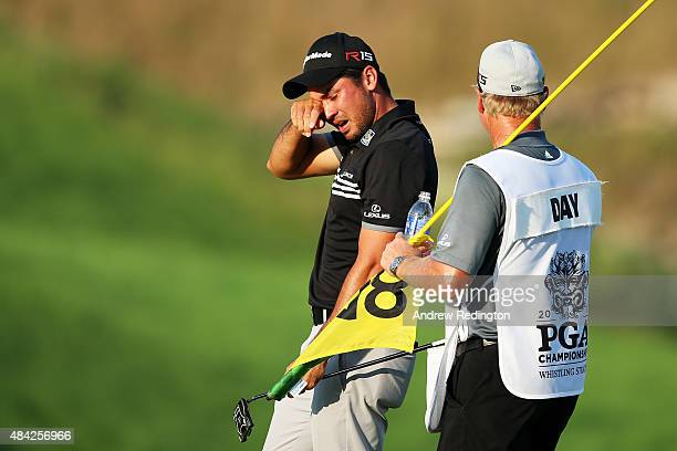 Jason Day of Australia celebrates with his caddie Colin Swatton on the 18th green after winning the 2015 PGA Championship with a score of 20under par...