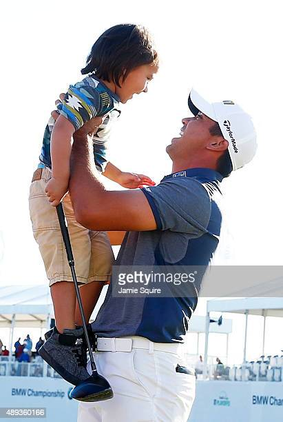 Jason Day of Australia celebrates with his son Dash after winning during the Final Round of the BMW Championship at Conway Farms Golf Club on...