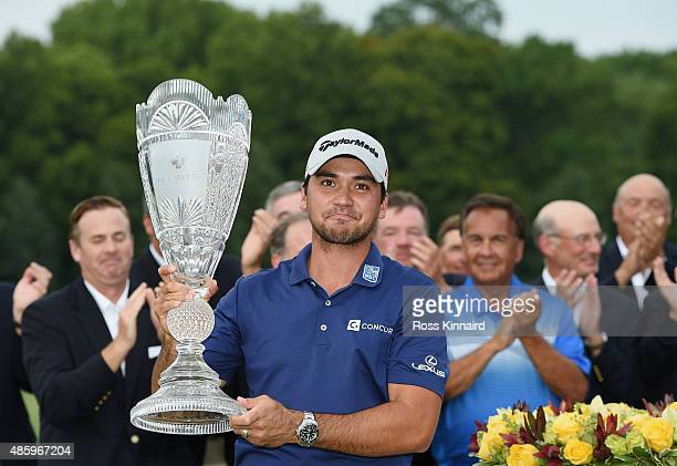 Jason Day of Australia celebrates with the winner's trophy on the 18th green after his sixstroke victory at The Barclays at Plainfield Country Club...