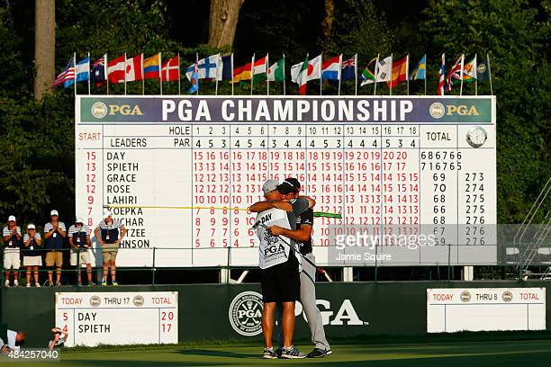 Jason Day of Australia hugs his caddie Colin Swatton on the 18th green after winning the 2015 PGA Championship with a score of 20under par at...