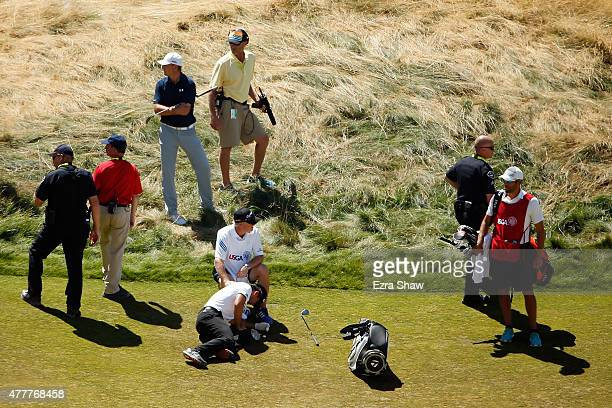 Jason Day of Australia is overcome by dizziness and lays on the ninth hole as his caddie Colin Swatton looks on during the second round of the 115th...