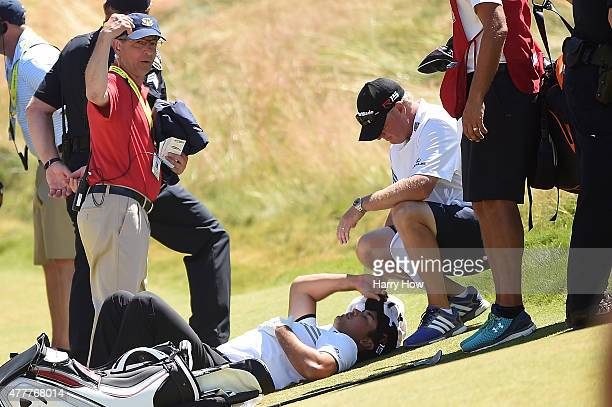 Jason Day of Australia is tended to by caddie Colin Swatton as he lays on the ninth green after falling due to dizziness during the second round of...