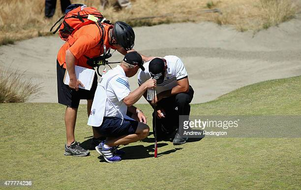 Jason Day of Australia is tended to by caddie Colin Swatton as he lays on the ninth hole after falling due to dizziness during the second round of...