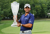 Jason Day of Australia poses with the winner's trophy on the 18th green after his sixstroke victory at The Barclays at Plainfield Country Club on...