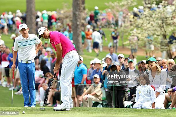 Jason Day of Australia putts as wis wife Ellie son Dash and Cameron Smith of Australia look on during the Par 3 Contest prior to the start of the...