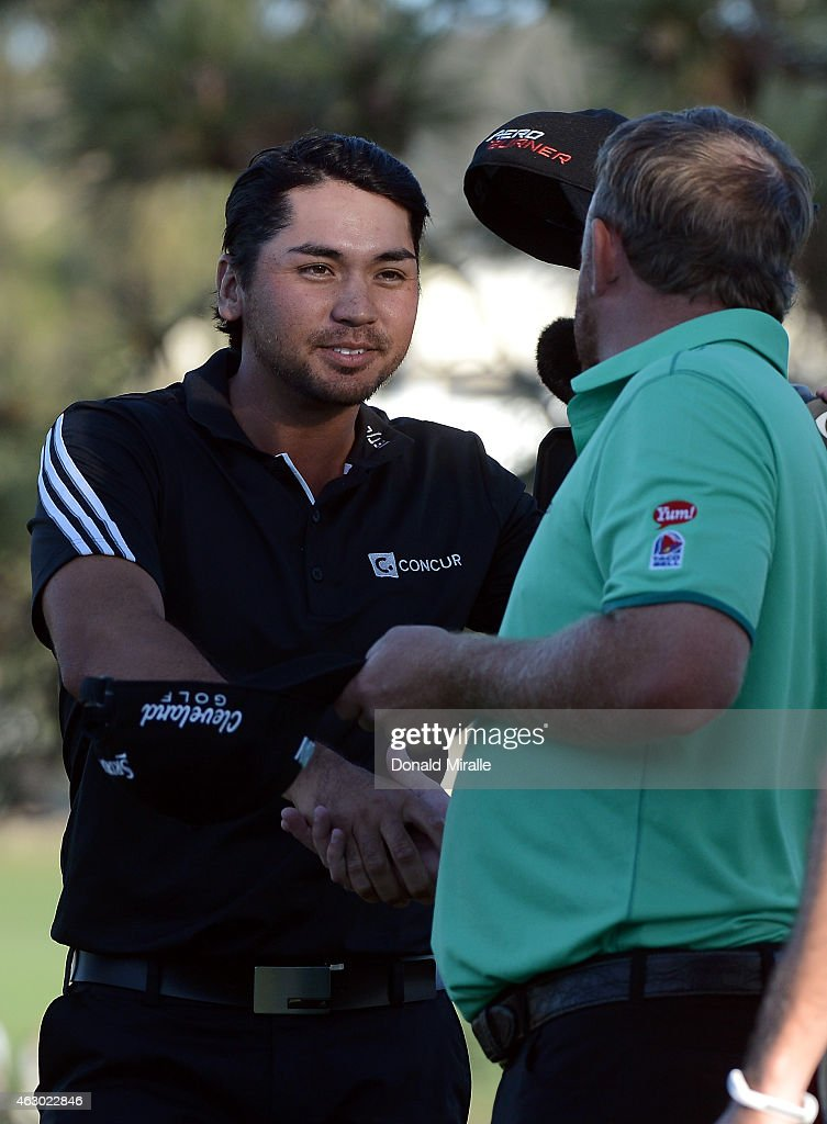 Jason Day (L) of Australia shakes hands with J.B. Holmes after the conclusion of their playoff on the 16th green during the final round of the Farmers Insurance Open at Torrey Pines South on February 8, 2015 in La Jolla, California.