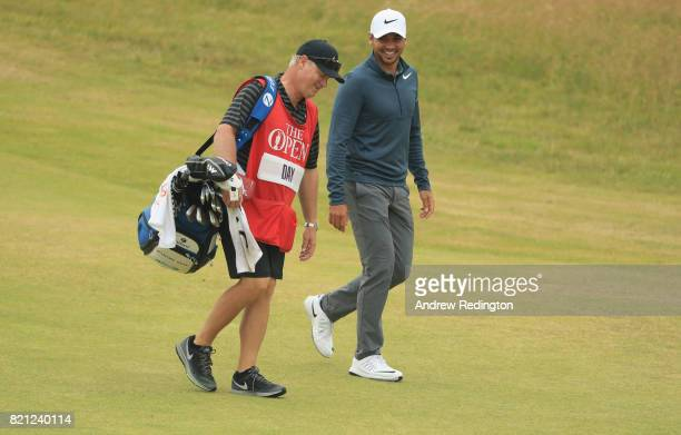 Jason Day of Australia smiles with his caddie walking up the 18th hole during the final round of the 146th Open Championship at Royal Birkdale on...