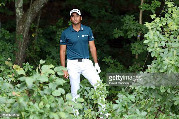 Jason Day of Australia stands in the trees as he looks to play his shot on the fifth hole during the second round of the Deutsche Bank Championship...