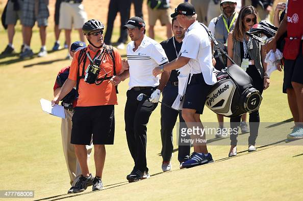Jason Day of Australia stands up after falling on the ninth green due to dizziness during the second round of the 115th US Open Championship at...