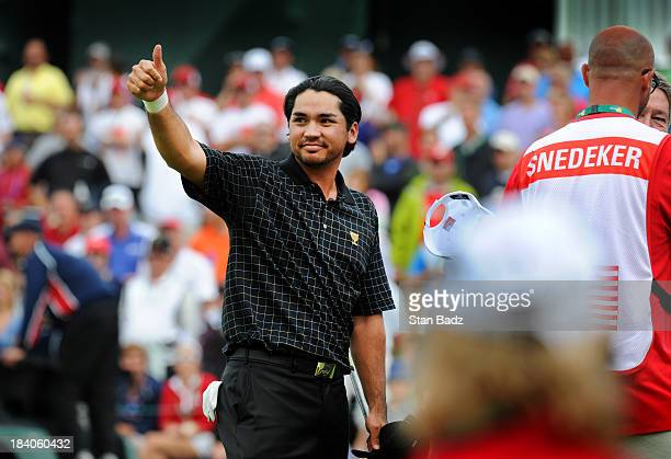 Jason Day of the International Team gives a thumbs up to the gallery after defeating Brandt Snedeker to win his match on the 14th hole during the...