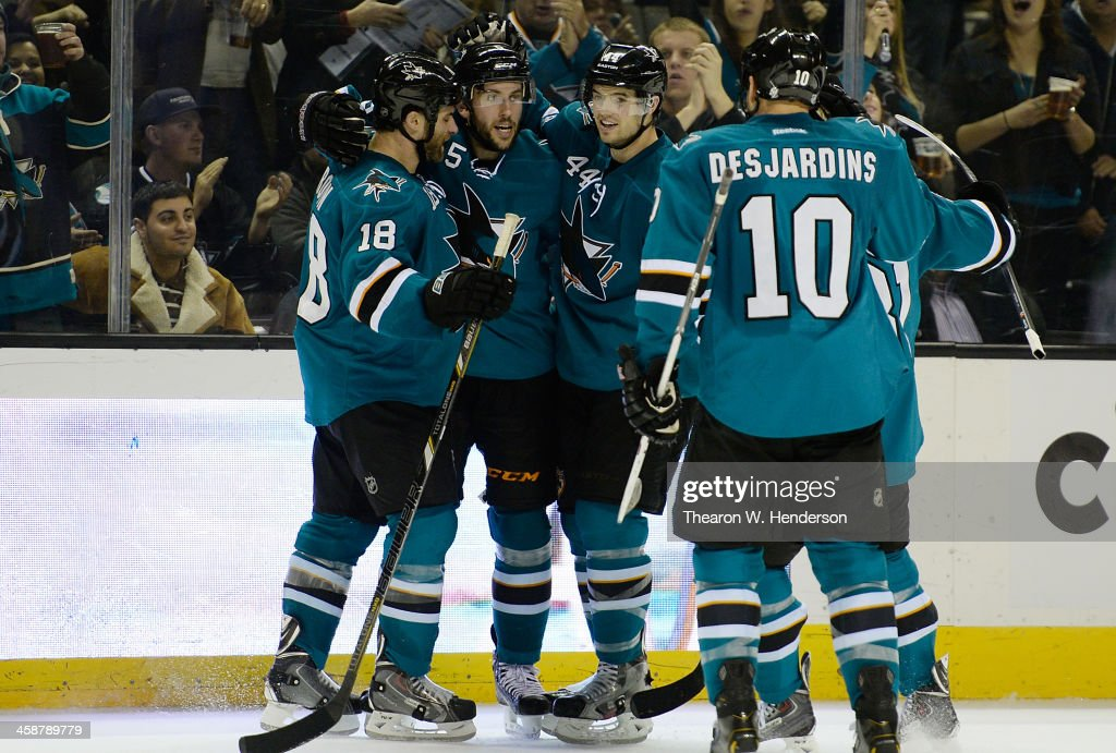 Jason Demers #5, Marc-Edouard Vlasic #44 and Mike Brown #18 of the San Jose Sharks celebrates after Demers scored a goal against the Dallas Stars during the second period at SAP Center on December 21, 2013 in San Jose, California.